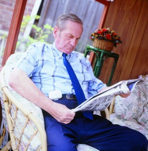 Man sat reading newspaper whilst reading a device that detects falls in the home