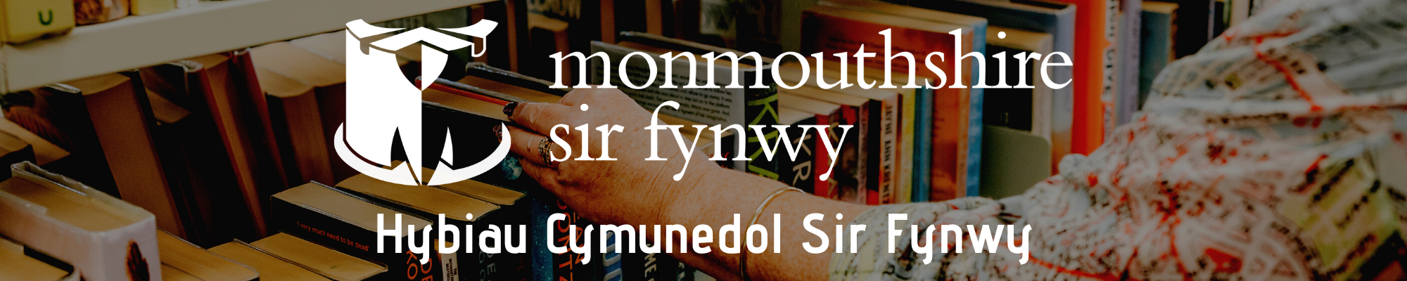 Photo of a library shelf with a ladies hand reaching for a book.  ON top of the background picture is the monmouthshire logo with the text 'Hybiau Cymunedol Sir Fynwy'
